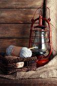 foto of kerosene lamp  - Kerosene lamp with yarn and needles for knitting in wicker basket on wooden planks background - JPG