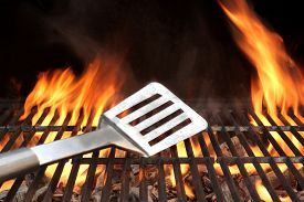 foto of charcoal  - Spatula on the Barbecue Charcoal Fire Grill with Black Background - JPG