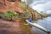 stock photo of horsetooth reservoir  - paddler in an decked expedition canoe approaching rocky sandstone shore  - JPG