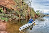 picture of horsetooth reservoir  - a senior paddler in an decked expedition canoe approaching rocky sandstone shore  - JPG