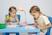 image of 6 year old  - Two girls of four and six years of sitting at the table and draws and paints and pencils - JPG