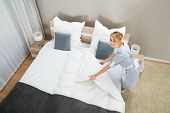 stock photo of housekeeper  - Female Housekeeper Making Bed With Bed Clothes In Hotel Room - JPG