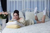 picture of short-story  - Laughing girl lying on the bed and reading a book - JPG