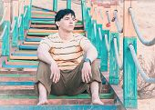 foto of barefoot  - Barefoot young man sitting on colorful stairs on the beach - JPG