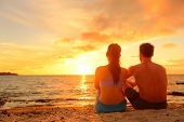 pic of couple sitting beach  - Happy Romantic Couple Enjoying Beautiful Sunset at the Beach Sitting in Sand looking at ocean sea and colorful yellow sky - JPG