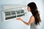 stock photo of air conditioner  - Young Woman Checking Air Conditioner In House - JPG