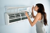 picture of air conditioner  - Young Woman Checking Air Conditioner In House - JPG