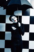 picture of mime  - Male mime artist stands under an umbrella in the rain and expressing different emotions - JPG