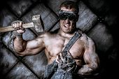 stock photo of mines  - Strong aggressive coal miner with a hammer over dark grunge background - JPG
