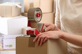 picture of packing  - Woman packs parcel in post office - JPG