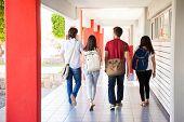 stock photo of walking away  - Rear view of a group of university students walking away on a school hallway  - JPG