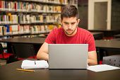 pic of student  - Handsome young college student using a laptop for school work in the library - JPG