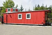 stock photo of caboose  - A freshly painted red caboose by the railway crossing - JPG