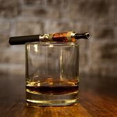 picture of electronic cigarette  - vintage still life with electronic cigarette and a glass of amber whiskey