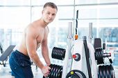 foto of toothless smile  - Confident young muscular man choosing weight to lift and smiling while standing in gym - JPG