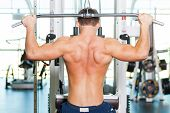 stock photo of work bench  - Rear view of young muscular man working out on bench press - JPG