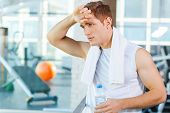 picture of forehead  - Tired young man carrying towel on shoulders and touching his forehead while standing in gym - JPG