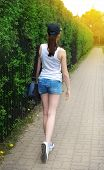 foto of stroll  - strolling girl in blue cap with green nature on background - JPG