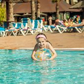 image of pool ball  - cute little girl playing in the pool with colorful ball - JPG