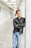 foto of jacket  - Attractive blond young man with leather jacket standing outside against pillar - JPG