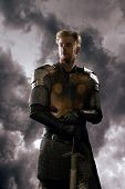 picture of cloudy  - Ancient knight in metal armor with sword standing on a cloudy background - JPG