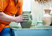 pic of loam  - On a rotating pottery wheel wizard manually manufactures ceramic vase - JPG