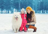 pic of children walking  - Portrait of happy family in winter day mother and child walking with white Samoyed dog in the park - JPG