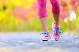 stock photo of crossed legs  - Walking and jogging woman with athletic legs and running shoes - JPG