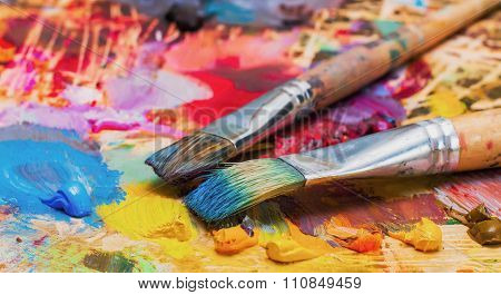 Used Brushes On An Artist\'s Palette Of Colorful Oil Paint