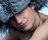 Portrait of handsome young man wearing fluffy hat poster