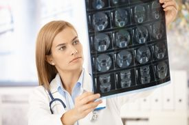 foto of x-files  - Young attractive female radiologist looking at x - JPG
