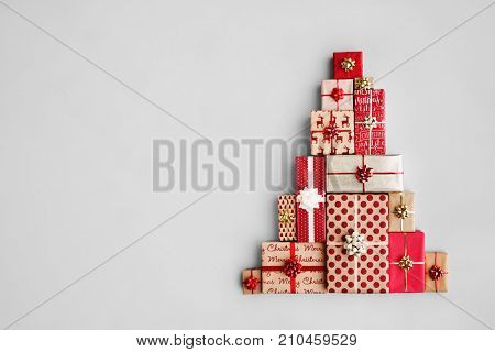 poster of Christmas gift boxes laid out in the shape of a Christmas tree, overhead view