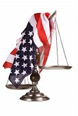 stock photo of scales justice  - Old beat up scale with an American flag draped over it - JPG