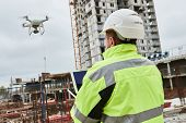 Drone operated by construction worker on building site poster