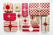 Collection of Christmas presents arranged on a white background, overhead view poster