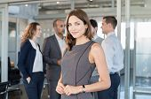Successful formal woman standing in front of businesspeople and smiling. Portrait of confident and p poster