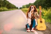 Beautiful hippie girl sitting with guitar on roadside outdoor. Contemporary bohemian style. Spirit o poster