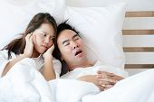 Couple On Bed With White Mattress Man Snoring Loud Makes Women Feel Annoyed. Causes Of Obstructive S poster