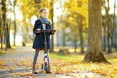 Adorable Young Girl Riding Her Scooter In A City Park On Sunny Autumn Evening. Pretty Preteen Child poster