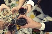 Top-down View Of Male And Female Hands With Filled Glasses Of Wine Above The Restaurant Tabletop. Dr poster