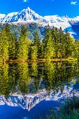 The lake reflected the evergreen spruce and snow-capped Alps. Concept of active and ecological touri poster