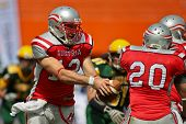 VIENNA, AUSTRIA - JULY 15: QB Thomas Haider (#13 Austria) hand off the ball to RB Mario  Nerad (#20