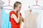 Young Blonde Long Hair Woman In Clothes In Shop Or Wardrobe Choosing Summer Outfit, Dresses Hanging  poster