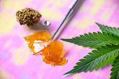 Macro detail of dab tool with cannabis concentrate aka shatter and marijuana leaf, cannabis extracti poster