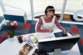 Front view of young pretty Asian female graphic designer using graphic tablet at desk in office. Thi poster