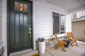 Home Facade With Glass Paned Front Door And Furniture On The Concrete Porch poster