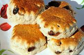 stock photo of devonshire  - Freshly cooked sultana scones stacked on a plate - JPG