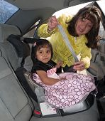 stock photo of seatbelt  - Natuve American woman placing her daughter in a child safety seat and fastening her seat belt - JPG