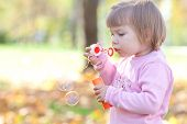 foto of leaf-blower  - beautiful little girl making bubble blower on the autumn forest - JPG