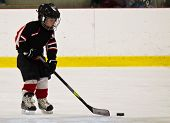 picture of hockey arena  - Child skating and playing hockey in an arena